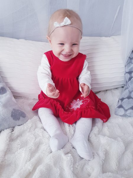 mała uśmiechnięta isiedzaca dziewczynka