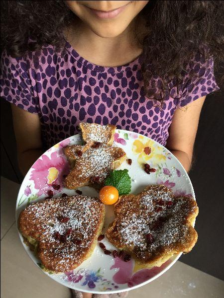 dziewczynka trzymajaca talerz zplacuszkami bananowymi wksztalcie serduszka, misia ikwiatka