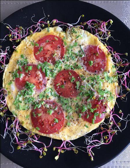Omlet zkiełkami ipomidorami naciemnym talerzu
