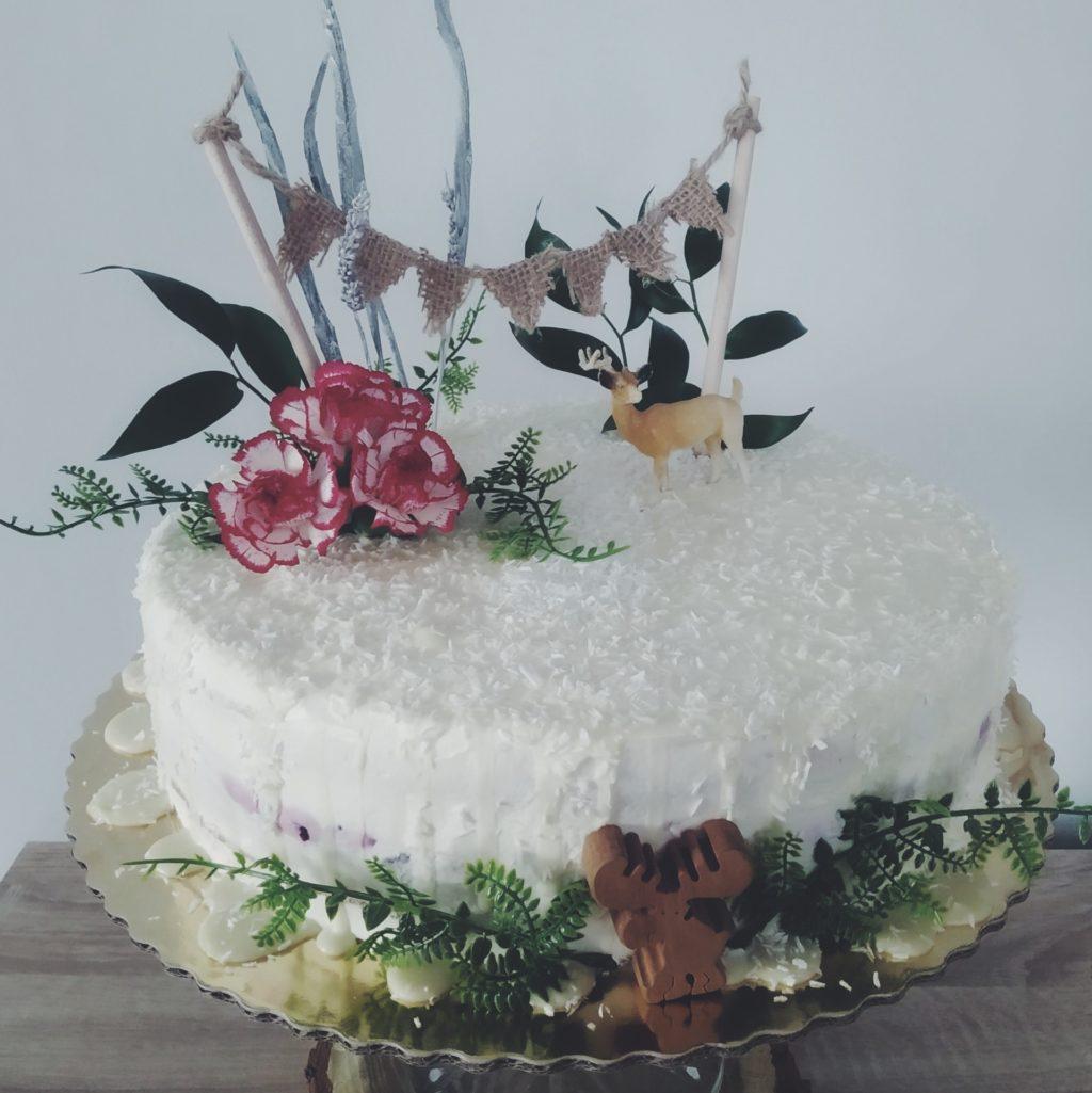 Tort zpolewą zbiałej czekolady udekorowany goździkami, zielonymi roślinami ifigurkami jelenia iłosia