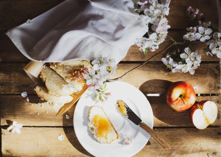 zdjęcie typu flat lay zrobione zlotu ptaka. Chałka, jabłka, kwiaty jabłoni. Natalerzyku kawałek chałki posmarowanej dżemem